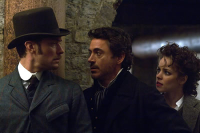 A man in Edwardian dress talks to a man and a woman in similar clothing, under an archway