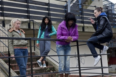 A group of teenage girls stand outside on some steps smoking