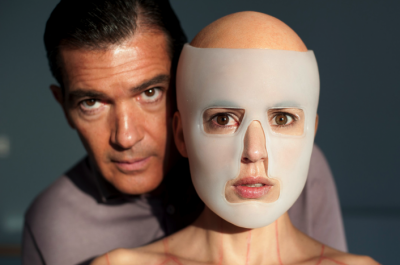 A man stands beside a woman wearing a plastic mask on her face