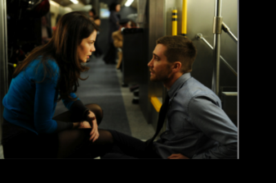 A man and woman look at each other in a concerned manner whilst crouching on a train carriage floor.