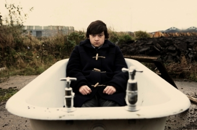 A teenage boy sits in a bath that has been abandoned on an industrial estate