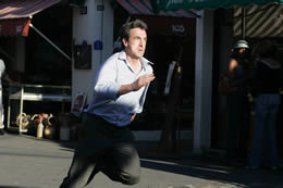 A man in a suit runs down a road looking worried