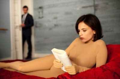 A woman reclines on a red cover wearing a skin-tone bodysuit, whilst a man hovers out of focus in the background.