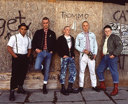 Still of five skinheads standing in front of a graffitied wall