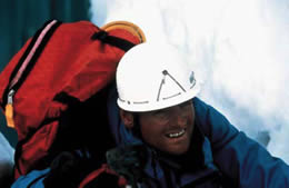 A man wearing a hard hat and a backpack climbs up a snowy rock