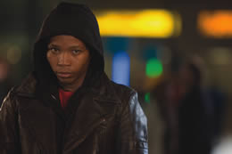 A boy in a hooded top stands in a street