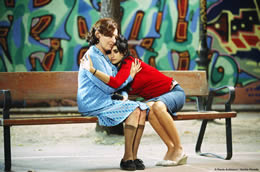 A young woman sits on a bench leaning to hug a woman sitting next to her