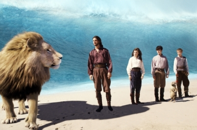 A lion, young man, a girl, two boys and a rat stand on a beach with a big wave behind them.