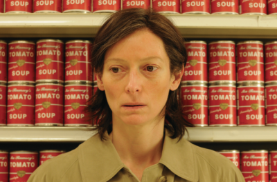 A woman stands in a supermarket aisle with cans of tomato soup on the shelves behind her