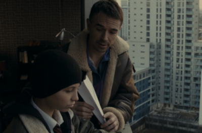 A man sits by a window holding a paper aeroplane and talking to a young boy who is standing beside him