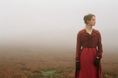 A young woman in a red dress stands on the moors surrounded by fog