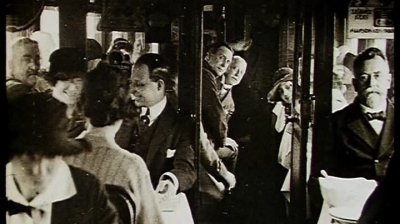 A group of people sit in the dining car of a train