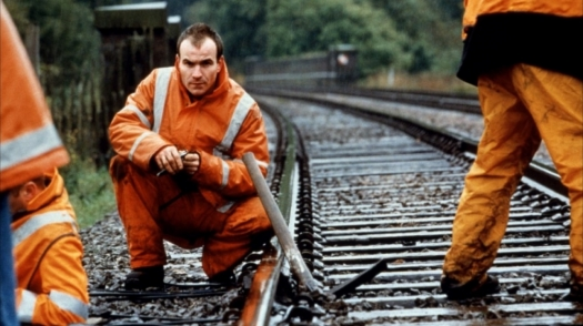 A man in an orange uniform crouches beside a train track