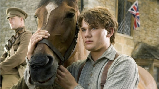 A boy stands holding a horse around its head with a soldier standing in the background