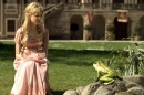 A young girl in a pink dress sits by a pond talking to a frog