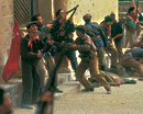Still image of a group of men fighting - red flag is held by one