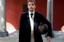 A man in a 3-piece suit stands in a courtyard holding a football under his arm