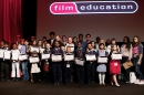 Lots of children of various ages stand on a stage with a man holding certificates and trophies.