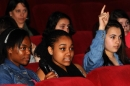 A row of girls sitting in a cinema, one with their hand in the air.
